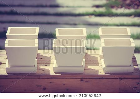 Close up row of white ceramic flowerpots on wooden box at outdoor garden in vintage style.