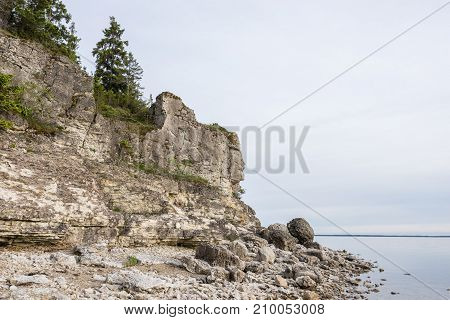 Sunset on the beach. Limestone cliff in the sea under blue sky and white clouds. Kesselaid a small island in Estonia. Nordic countries Europe