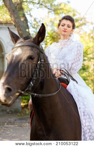 Beautiful bride in a wedding white dress riding a horse. The concept of a wedding.