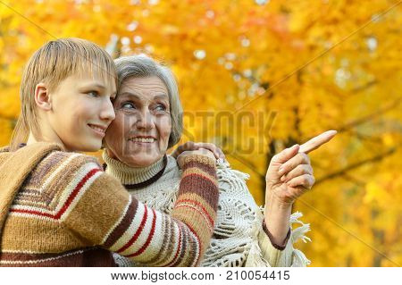 Grandmother and grandson hugging in autumn park