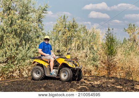 Caucasian man in sport protective goggles riding an ATV quad bike over rough terrain with meadows of dry autumn grass. Adventure activity concept.