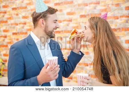 A man is feeding a girl a piece of pizza. In the office. They have festive hats on their heads. The concept of a holiday.