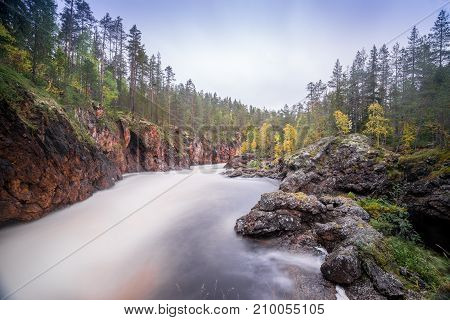 Red cliff stone wall forest waterfall and wild river view in autumn. Fall colors - ruska time in Kiutaköngäs. One part of Karhunkierros Trail. Oulanka National Park north Finland Lapland Europe