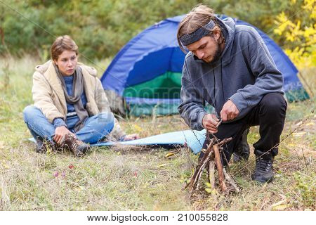 Couple in the forest. A man kindles a fire among dry branches. The girl is sitting near the tent.