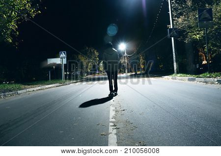 a mysterious man stands alone in the street among cars in an empty city walks the night street dreams