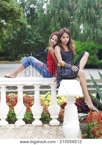 Girlfriends in summer park in a flower bed.