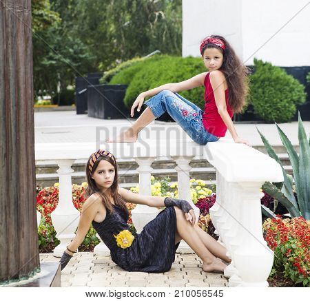 Portrait of two beautiful young women against a background of city park. Two sisters and girlfriends.