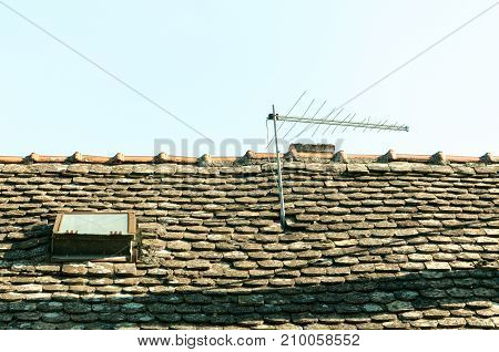 Classic vintage analog television antenna on the old house roof with tiles and window