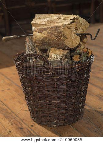 wicker basket full of chopped wood and fire-hook on wooden board floor