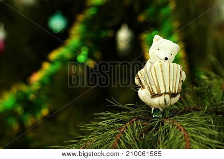 retro glass hand painted Christmas ornament - white bear-accordionist- on a background of a blurred Christmas tree