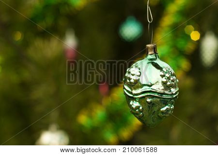 vintage glass Christmas ornament - strange ball nut or berry - on a background of a blurred Christmas tree