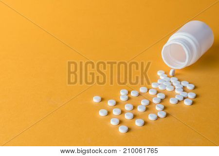 Pills spilling from an open bottle isolated on orange background