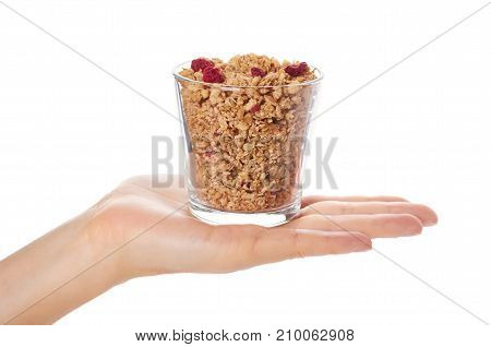 Homemade Granola With Dried Fruits In Glass Cup In Hand Isolated On White Background