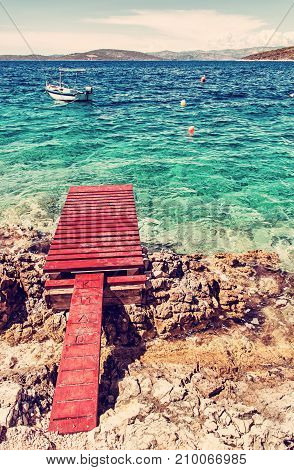 Beautiful Mediterranean sea Solta Croatia. Summer vacation. Springboard turquoise water and little boat. Red photo filter.