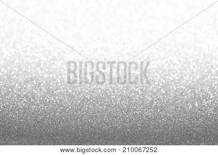Silver (gray) glitter background. Sparkle texture. Abstract gradient background blurred for New Years or Christmas holiday