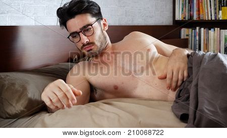 Young Handsome Shirtless Sleepy Man, Lying in Bed as He's Waking Up