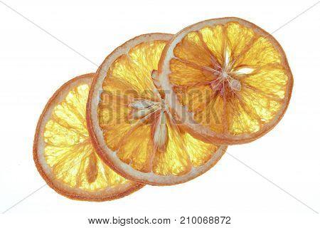 Diagonal arrangement of three slices of dried orange on white background