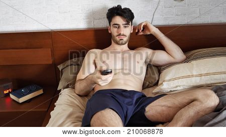 Young topless athletic man waking up in his bed then turning TV on with remote control in the morning