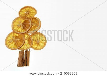 Christmas tree made from dried orange slices and cinnamon sticks on white background