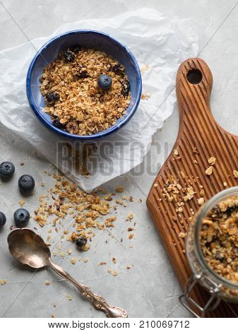 Homemade granola in a glass jar and in a bowl with fresh blueberries on a gray background
