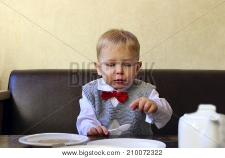 Cute small little boy sitting at wooden table with empty plate.