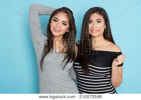 Two happy teen hispanic friends on blue background