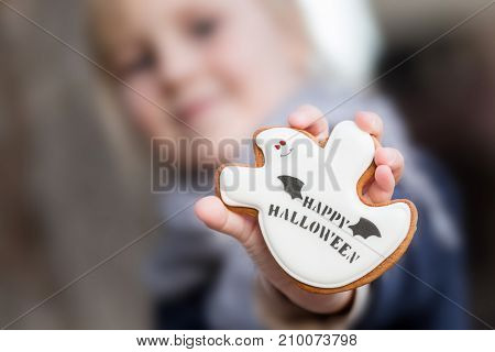 Little Cute Blonde Girl Holding A Homemade Ginger Honey Cookie In The Form Of Smiling Kind Ghost Wit