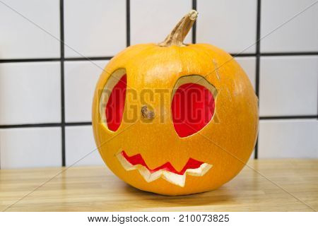 Traditional Halloween Big Orange Pumpkin With Kind Scary Smile And Big Red Glowing Eyes Standing On