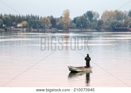 BELGRADE SERBIA - OCTOBER 22 2016 Fisherman fishing on the Danube river on his rowing boat during a warm autumn afternoon in Zemun a northern district of Belgrade