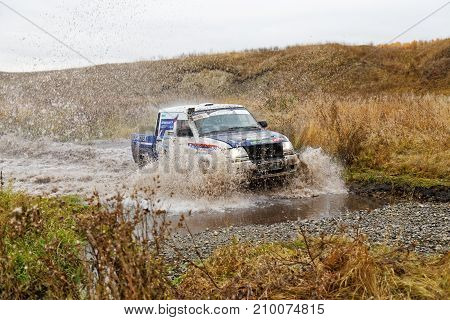 Rally Car Overcomes Water Obstacle Surrounded By Splashes.