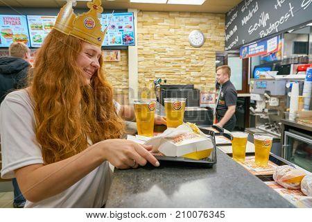 SAINT PETERSBURG - CIRCA OCTOBER, 2017: woman with a cardboard crown at Burger King restaurant. Burger King is an American global chain of hamburger fast food restaurants.