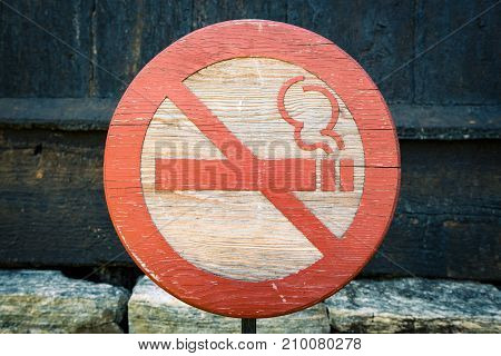 No smoking wooden sign with red cigarette crossed out