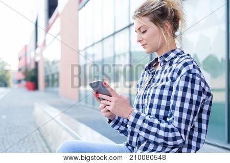Girl Holding Mobile Phone On City Street Background