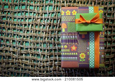 Stack of birthday gifts in vintage wrapping paper in greens and orange on heavy woven background horizontal aspect
