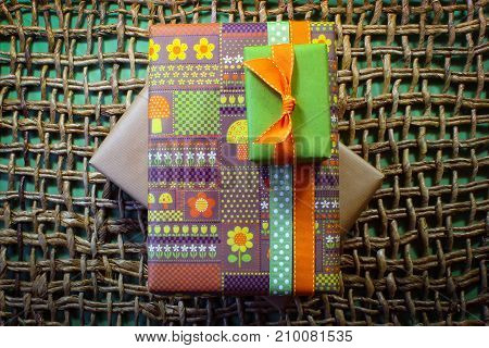 Vintage paper wrapped gifts on woven mat with green background centered horizontal aspect