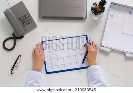 medicine, healthcare, cardiology and people concept - doctor hands with cardiogram, phone and laptop computer at table