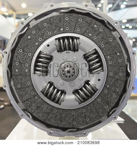 Front view of new composite clutch disc inside open housing for trucks and tractors. New friction pads. Clutch repair kit. Car maintenance parts. Clutch design. Round automotive background pattern