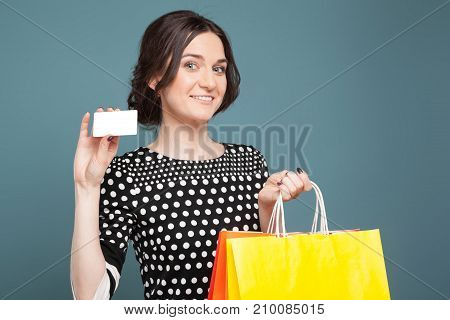 Image Of Beautiful Woman In Speckled Clothes Standing With Purchases And Cutaway In Hands