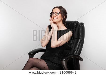 Picture Of Beautiful Woman In Black Dress Sitting In The Armchair