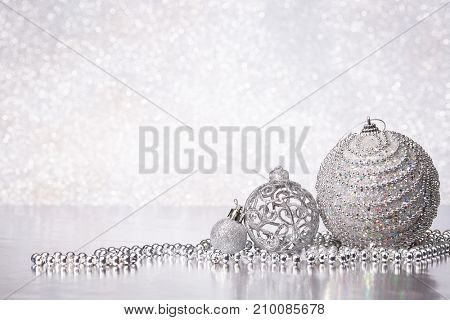 Christmas decoration with silver balls and garlands lying on a silvery background. New year and Christmas background with copy space for text. Greeting card.