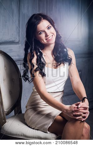Laughing girl in an elegant white dress sitting on a chair and smiling. Lens flare art effect.