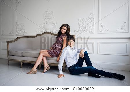 Happy pregnant couple at home, young loving family pregnancy, Portrait of man and woman expecting baby sitting at home on a sofa over luxury wall.