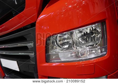 MOSCOW, SEP, 5, 2017: View on red MAN truck front light and radiator grille. Commercial Transport ComTrans-2017. Red truck light close up. Car light. Truck engine grill hood. Truck led light