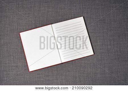 Opened red book on the dark grey sofa