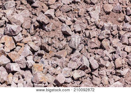 Industrial earthworks blasting rocks spread closeup textures background overhead photo.