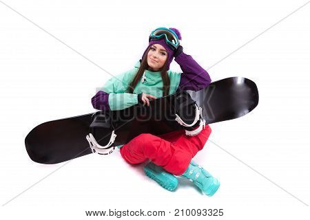 Young Woman In Purple Ski Outfit Hold Snowboard On Knees