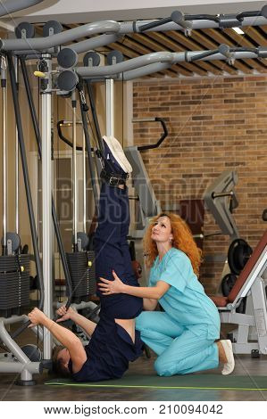 Young redhead female physiotherapist helps patient to rehabilitate using special equipment
