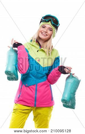 Beautiful Young Blonde Woman In Colorful Snow Coat Hold Snow Boots