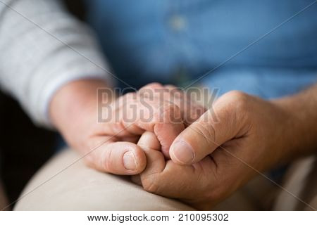 relationships, charity, old age and people concept - close up of senior couple holding hands