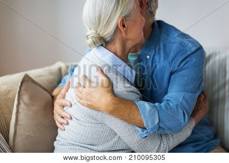 relationships, old age and people concept - close up of happy senior couple hugging at home